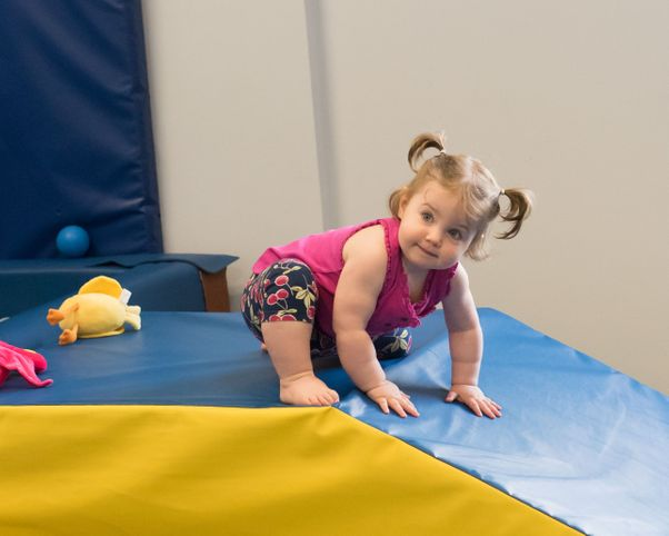 A toddler on a ramp representing sensory integration offered by sensory integration therapy clinic South Shore Therapies in Southern MA